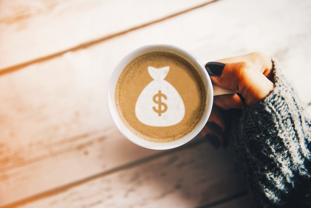 girl with a cup of coffee with a money bag symbol picture id660234910